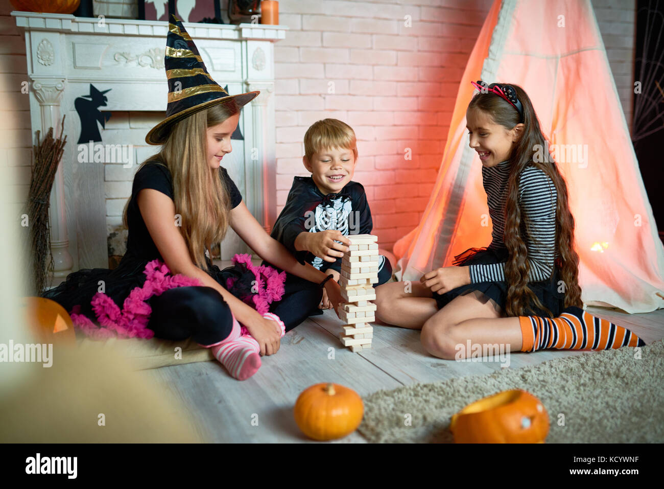 Joyful group of little friend wearing fancy costumes gathered together at Halloween home party and playing board - Stock Image