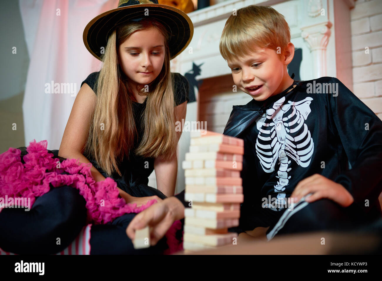 Handsome little boy and his pretty elder sister wearing Halloween costumes sitting on floor of living room and playing - Stock Image