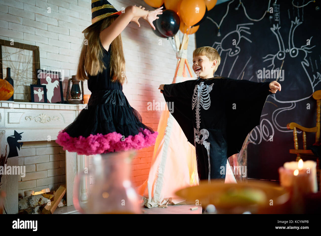 Cheerful children wearing Halloween costumes holding rehearsal before taking part in trick-or-treating, interior - Stock Image