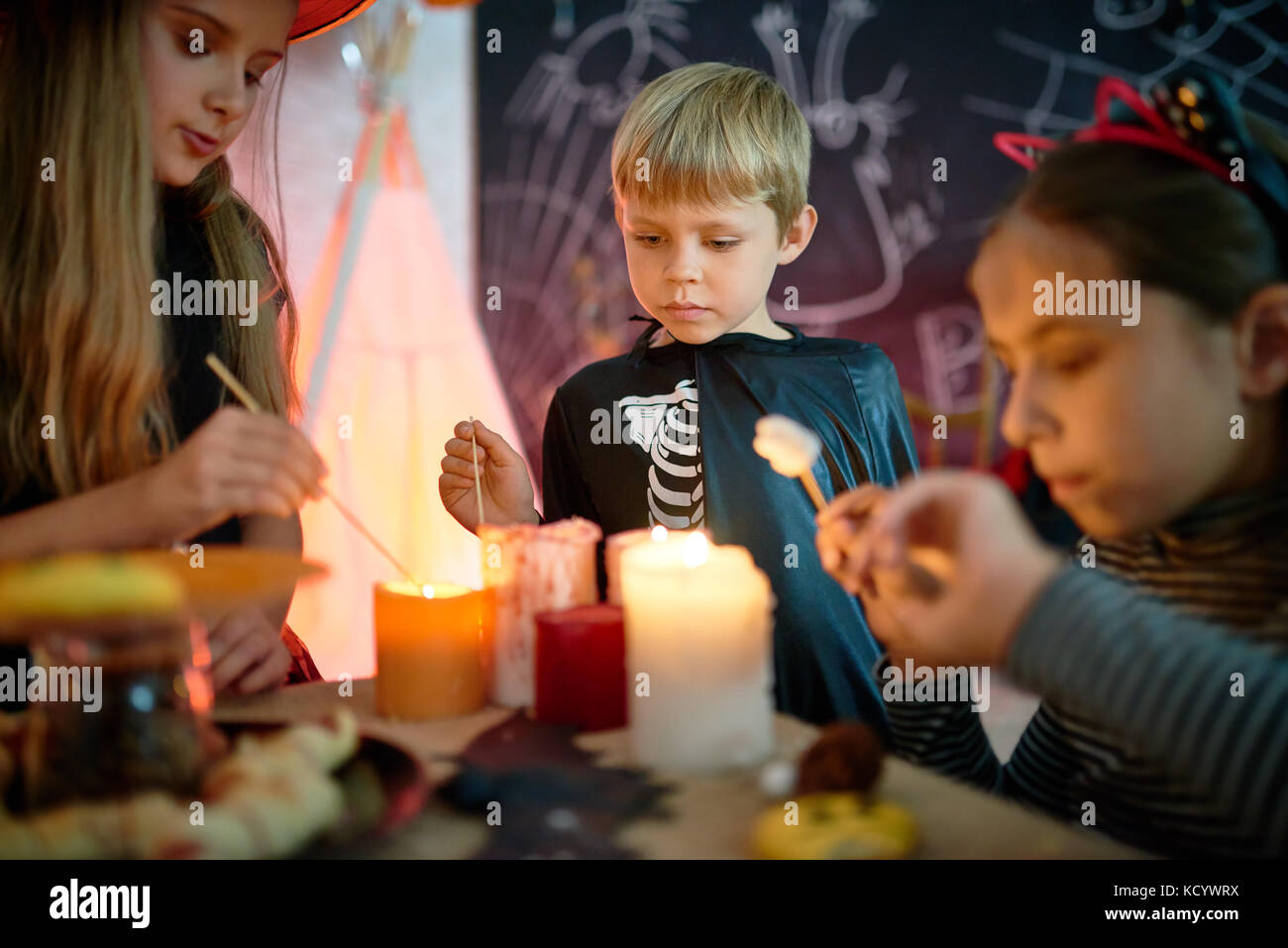 Three little friends wearing Halloween costumes gathered together at cozy living room decorated for holiday and - Stock Image