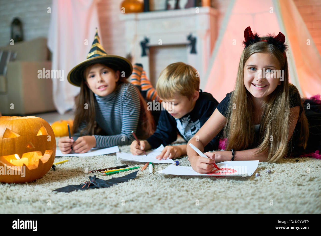 Group portrait of cheerful children wearing Halloween costumes gathered together at cozy living room decorated for - Stock Image