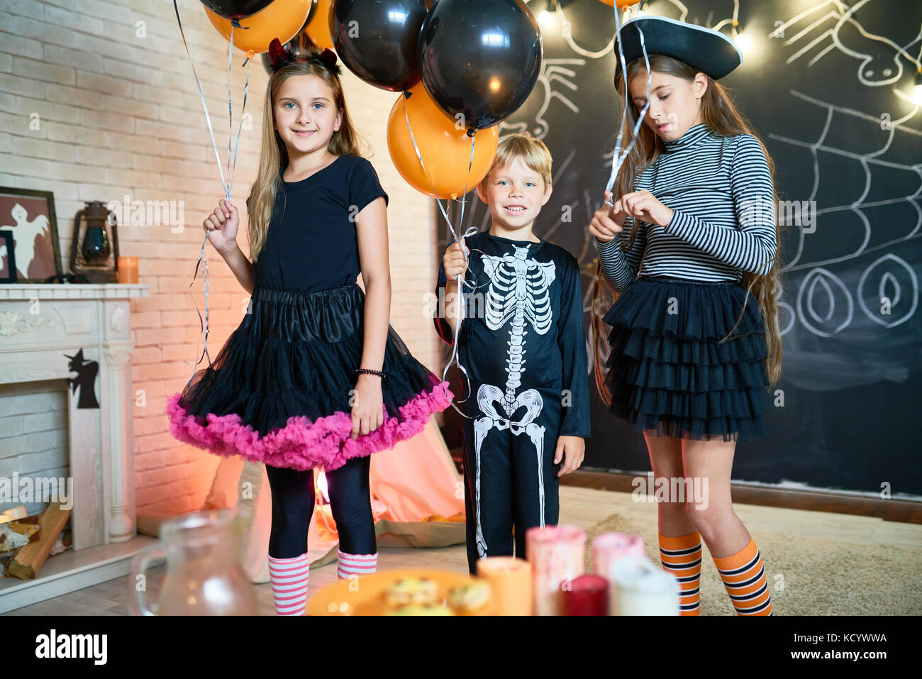Group portrait of smiling little friends wearing fancy costumes holding bunches of balloons in hands while posing - Stock Image