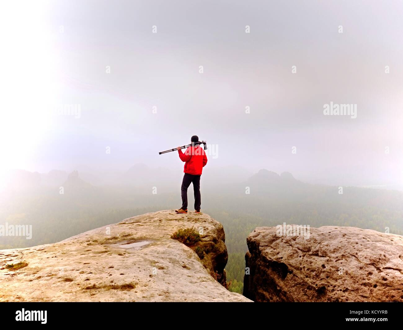 Nature photographer prepare camera to takes impressive photos of misty fall mountains. Tourist photographer at sharp - Stock Image