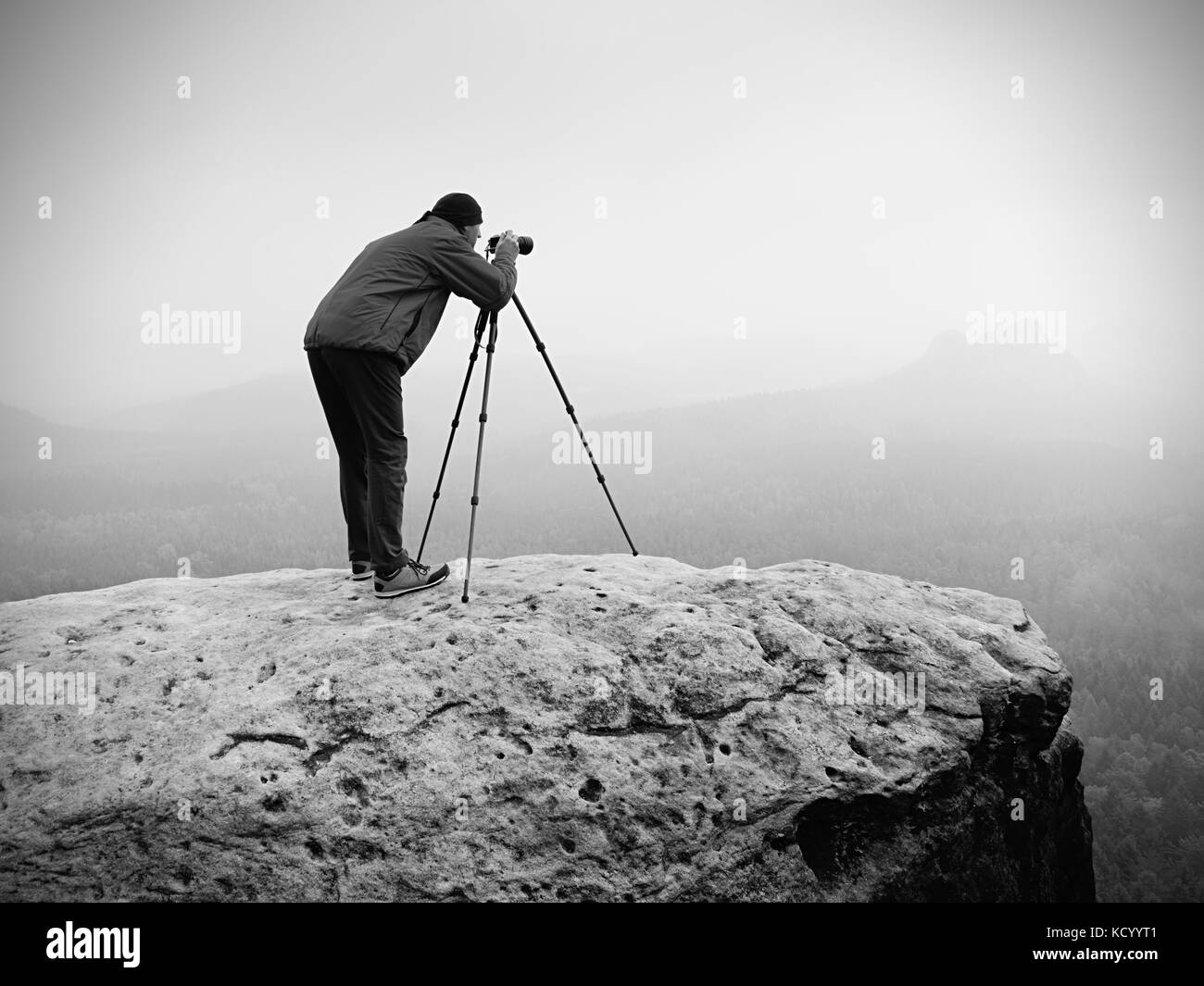 Wildlife photographer on mountain summit works. Man like to travel and photography, taking pictures of moments during - Stock Image