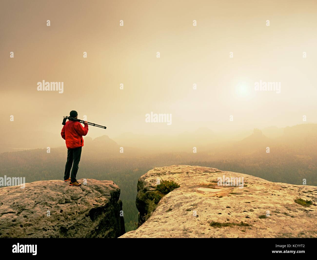 Professional photographer on location takes photos with mirror camera on peak of rock. Dreamy foggy landscape, spring - Stock Image
