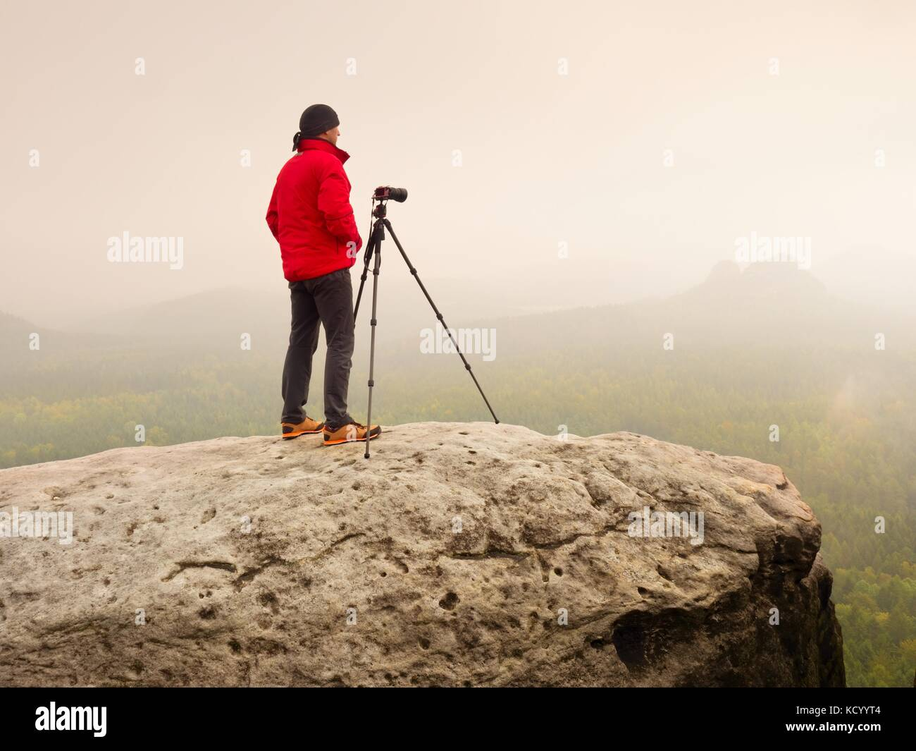 Photographer think about picture on peak  in the misty mountains. Photograph at daybreak above valley hidden in - Stock Image