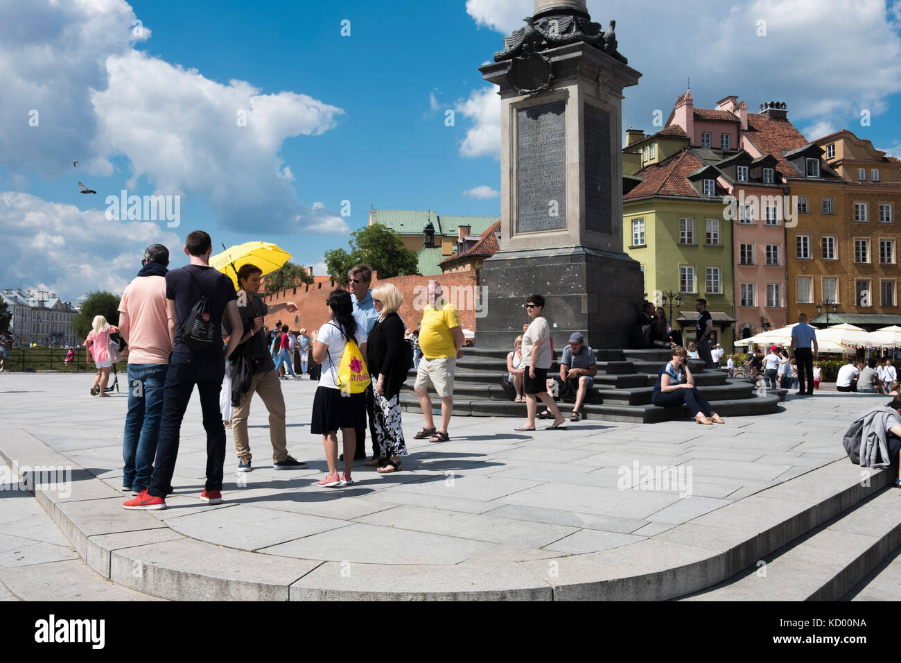 Tourists and tour guide with yellow umbrella, in front of the Sigismund III Vasa Column and colourful houses in - Stock Image