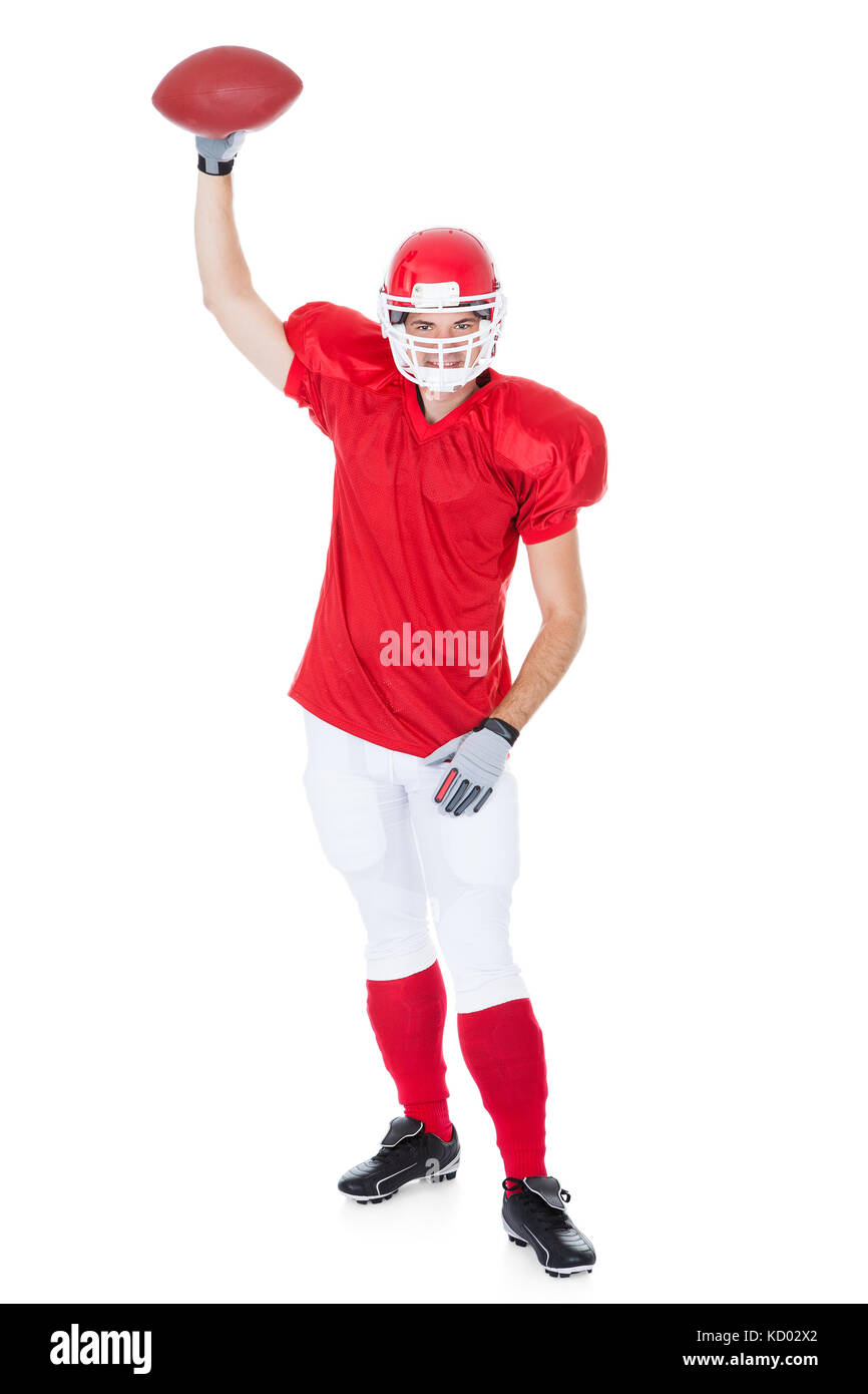American Football Player Holding Rugby Ball On White Background - Stock Image