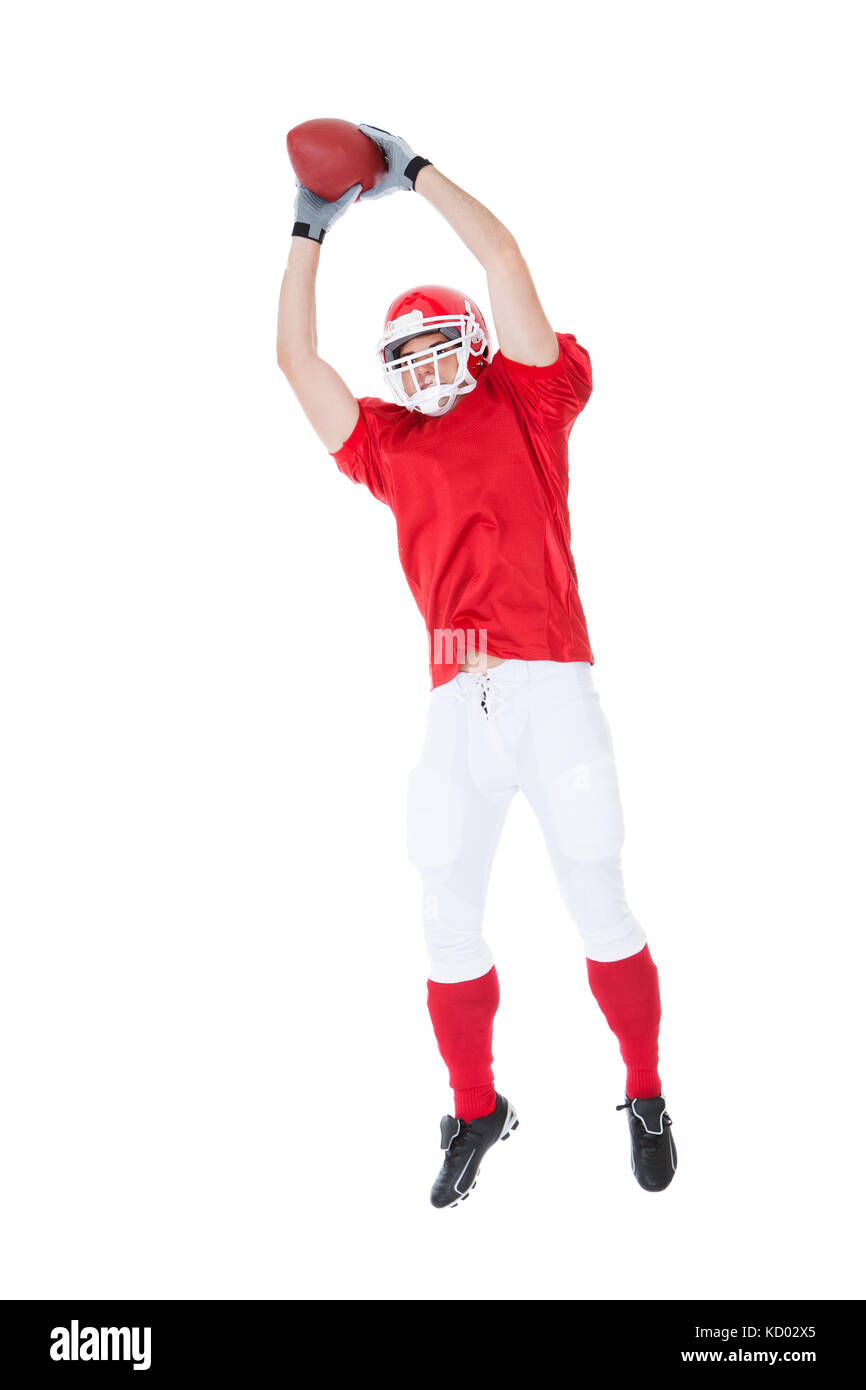 American Football Player Catching Ball On White Background - Stock Image