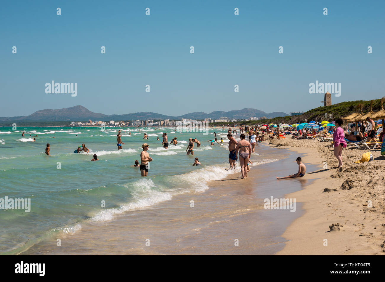 Tourists in Playa de Muro beach with Can Picafort town and mountains in background, northern part of Majorca island - Stock Image