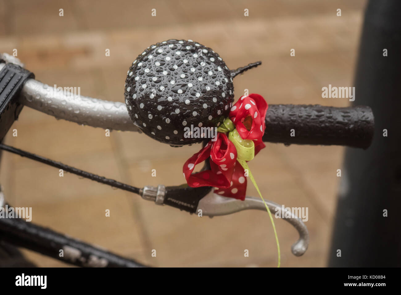 Wet bike bell with a colorful bow Stock Photo