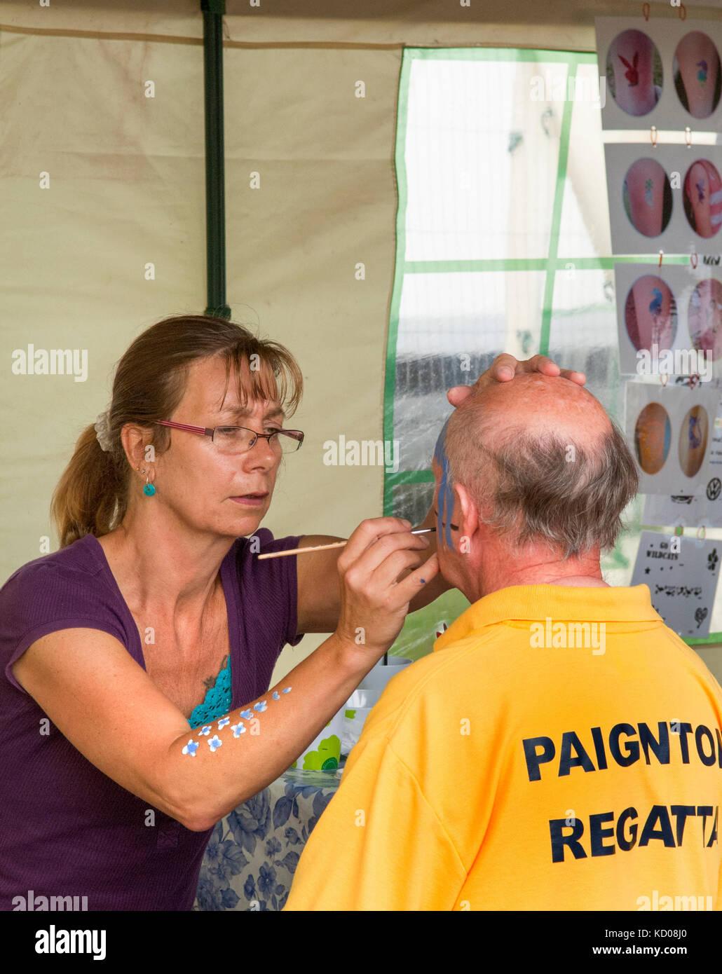Older Lady Face Painting A Balding Man Staff At Paignton Regatta