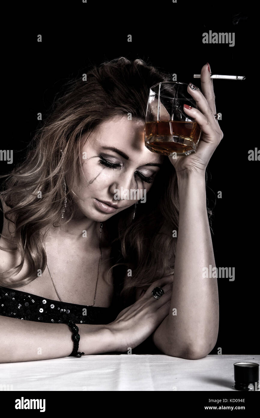Depressed young woman with a glass of whiskey and a cigarette over black background - Stock Image