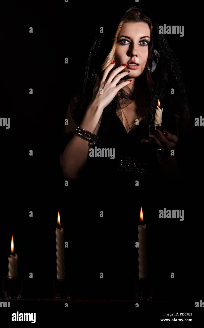 Scared young woman with a candle in darkness - Stock Image