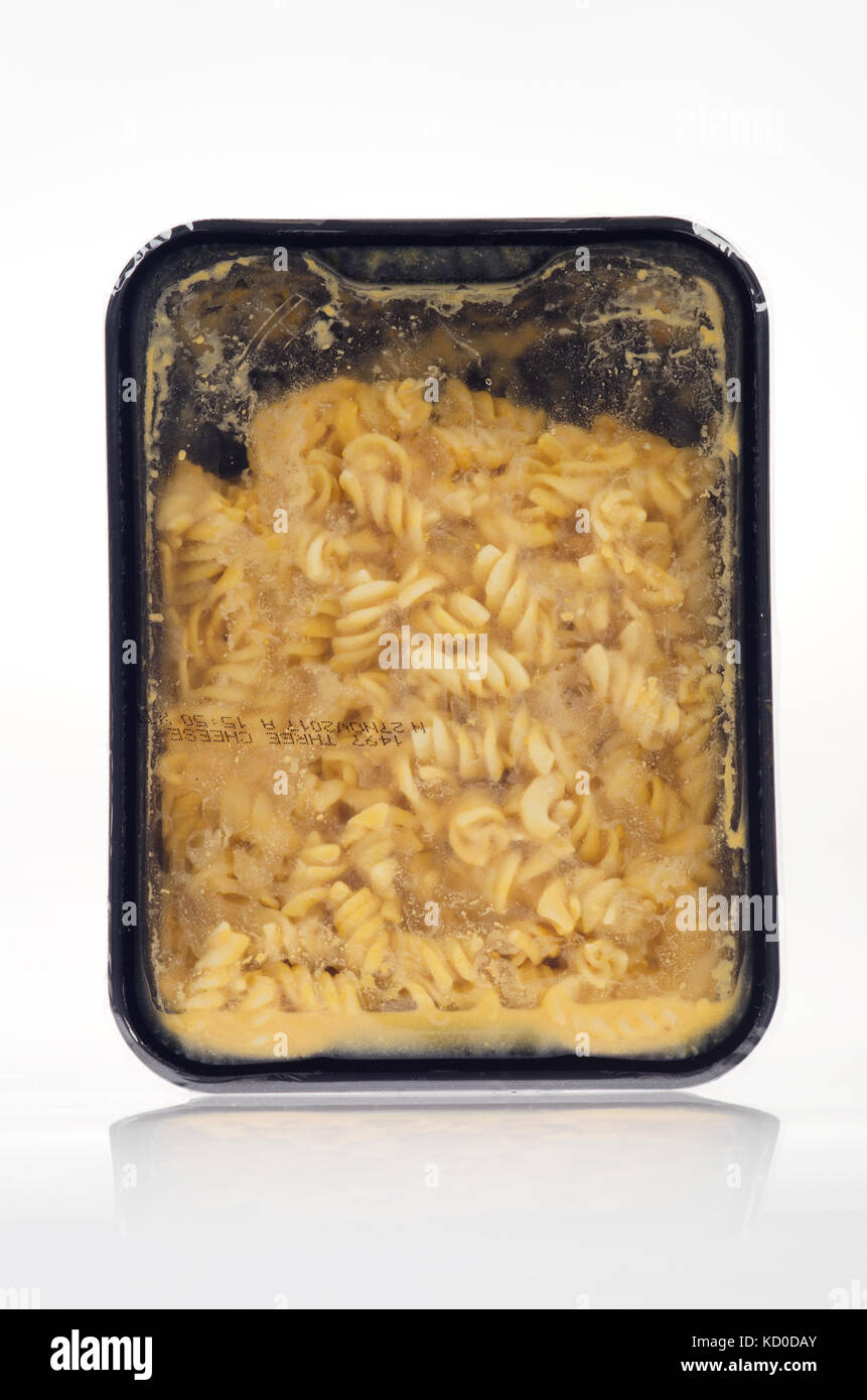 Tray of uncooked prepared Mac n Cheese with rotini pasta on white background, cut out - Stock Image