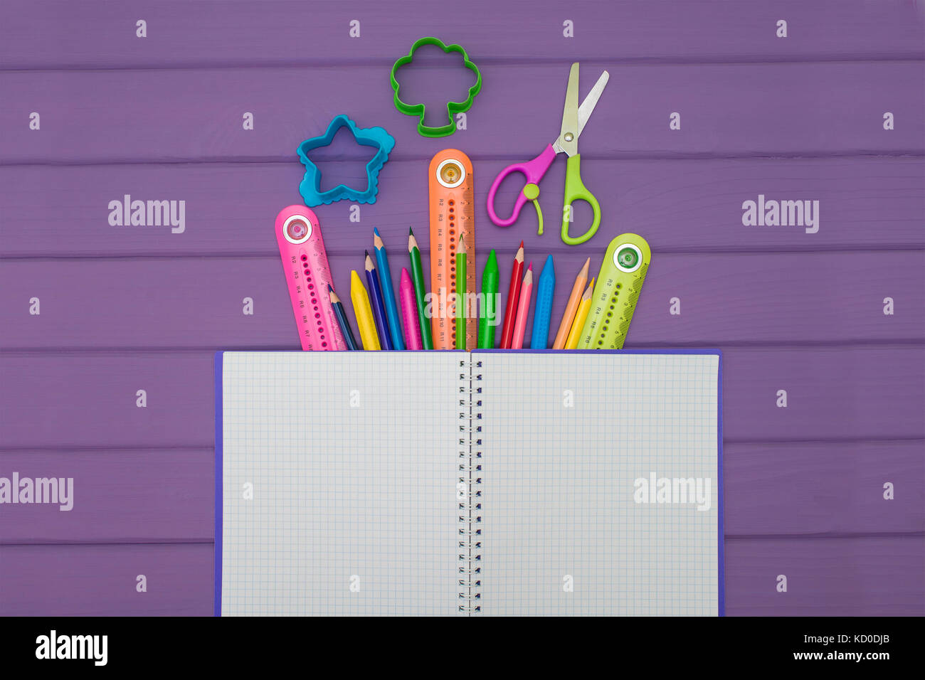 A notebook with colored pencils, rulers and scissors - Stock Image