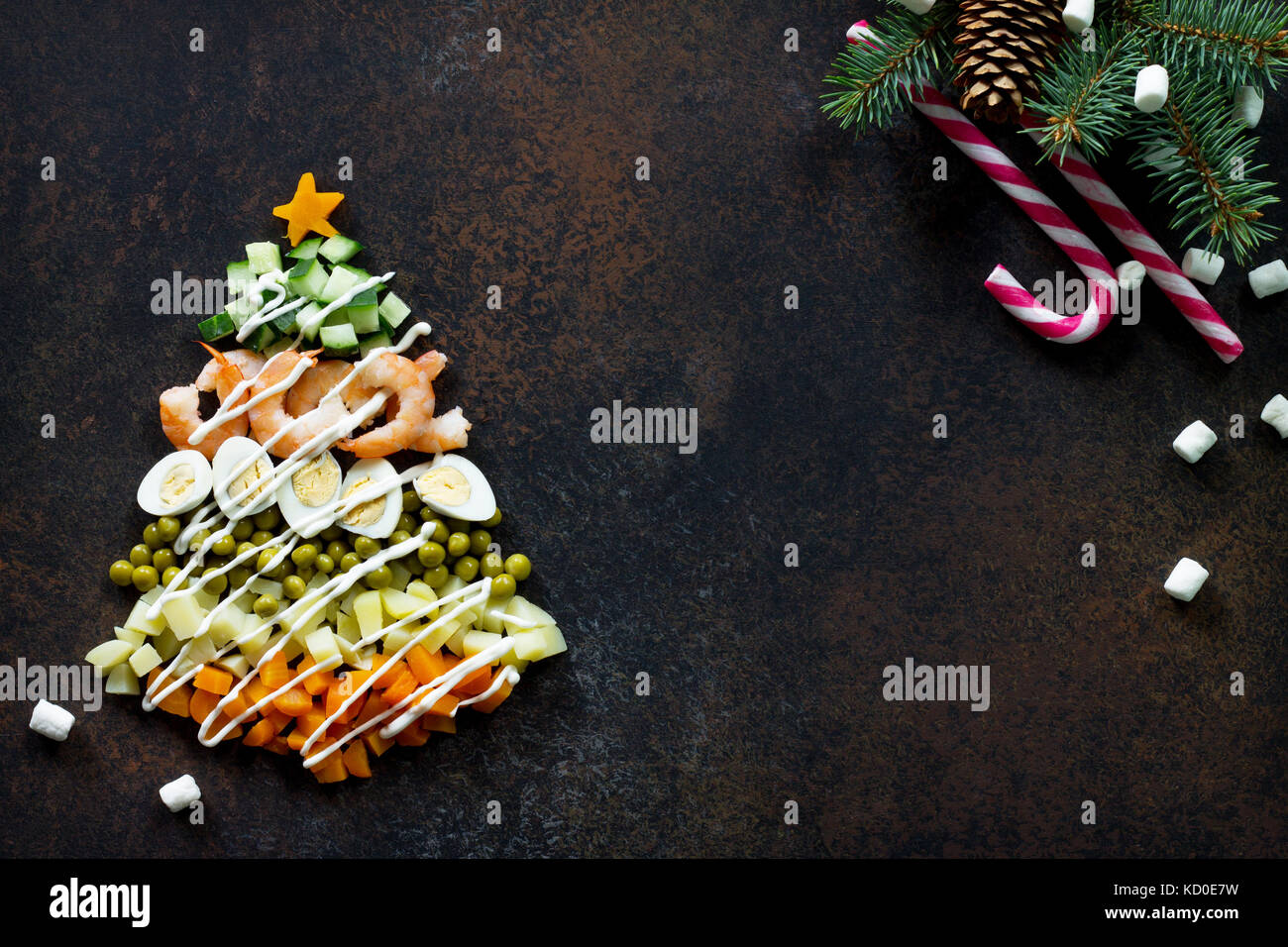 Christmas tree from a salad olivier on a brown rusty stone or metal background. Top view with a copy. Stock Photo