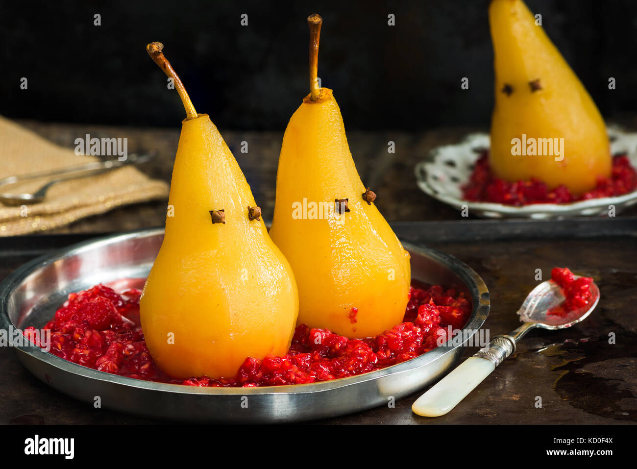 Pears poached in sweet syrup on crushed raspberries, presented as ghosts. Halloween food idea. - Stock Image
