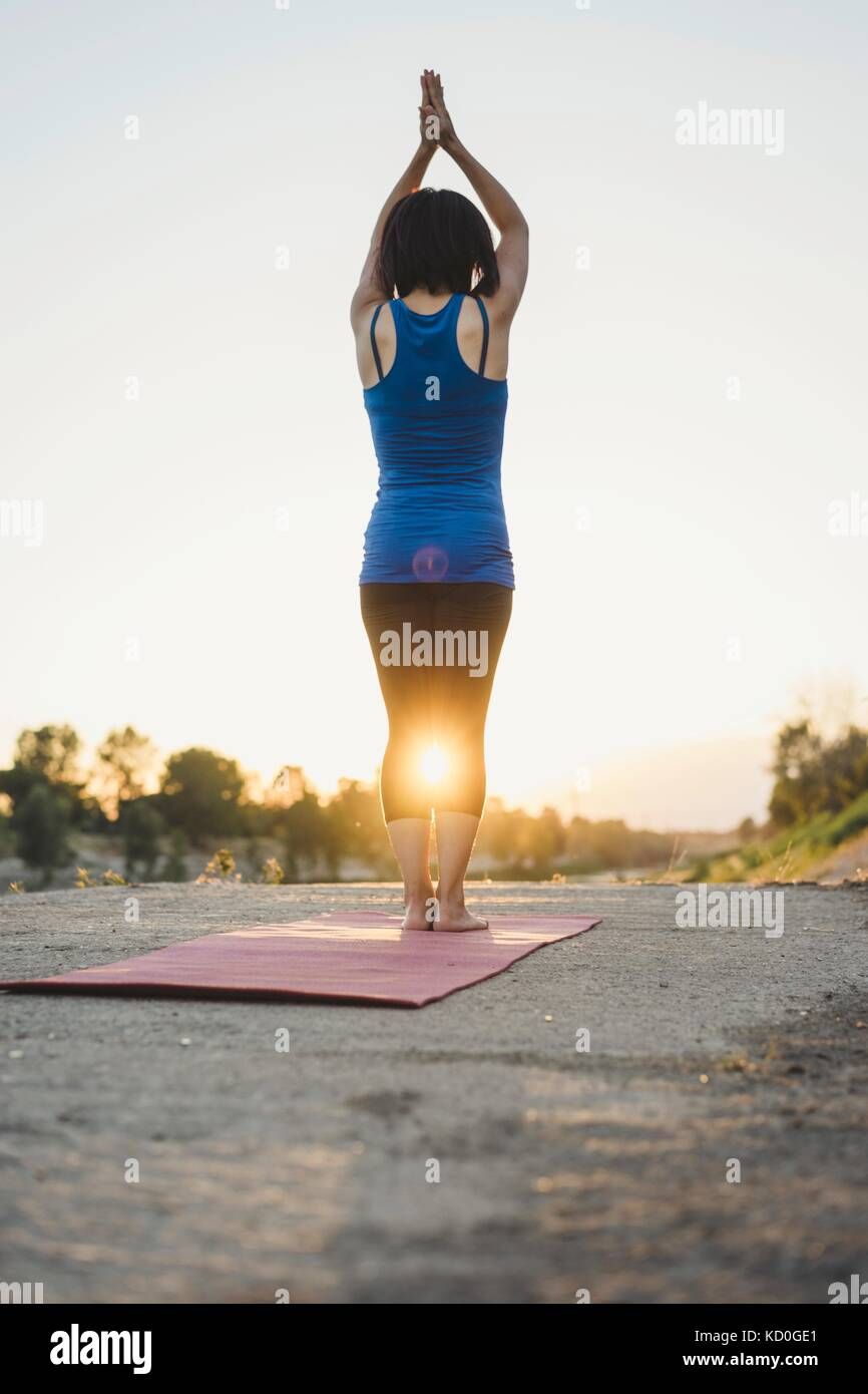 Mature woman outdoors, standing in yoga position, rear view - Stock Image