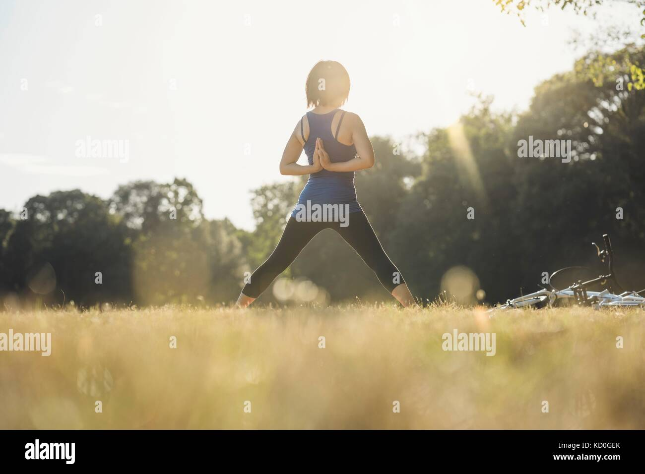 Mature woman in park, standing in yoga positions, hands behind back, rear view - Stock Image
