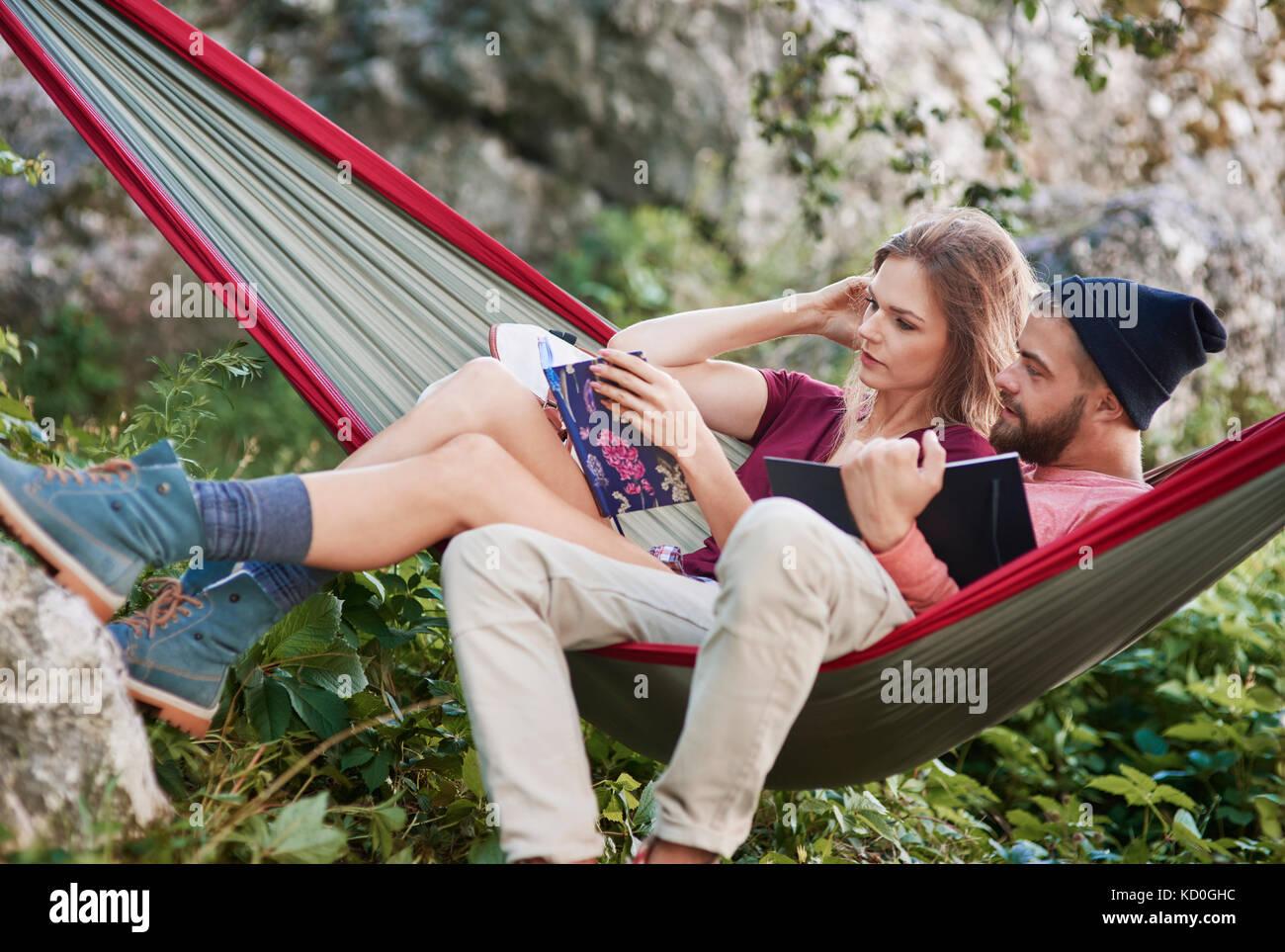 Couple relaxing in hammock reading books, Krakow, Malopolskie, Poland, Europe - Stock Image