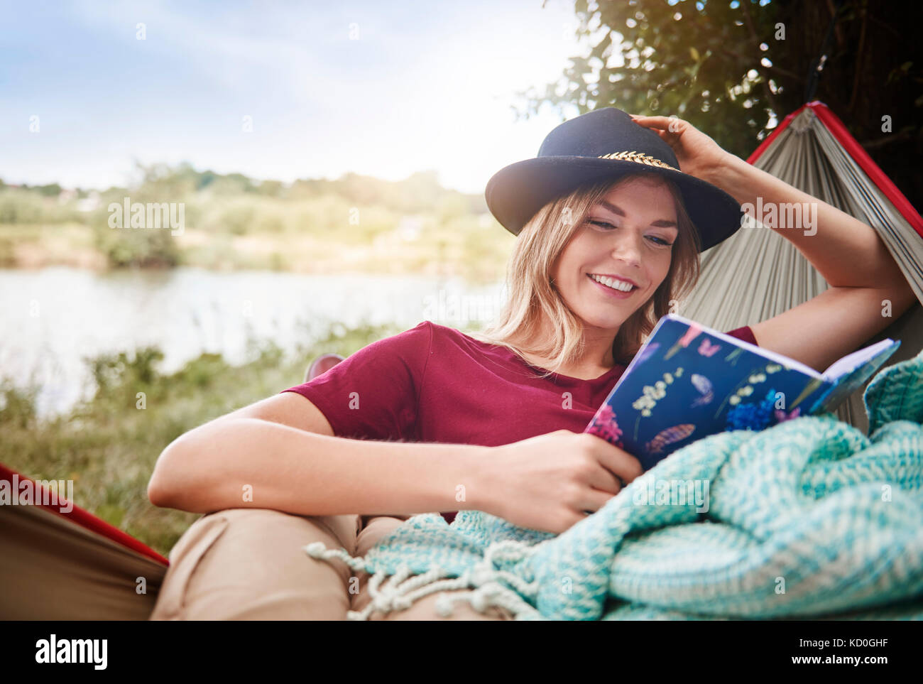 Woman relaxing in hammock reading book, Krakow, Malopolskie, Poland, Europe - Stock Image