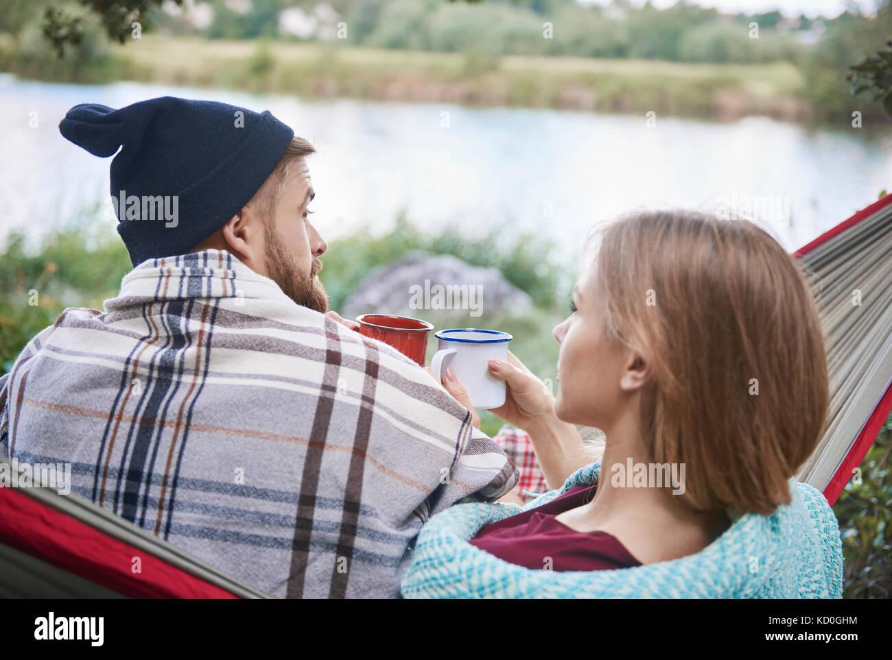 Rear view of couple in hammock holding enamel mugs, Krakow, Malopolskie, Poland, Europe - Stock Image
