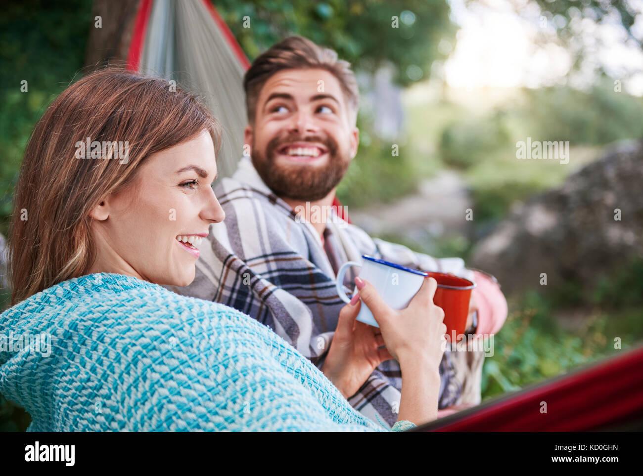 Couple in hammock holding enamel mugs smiling, Krakow, Malopolskie, Poland, Europe - Stock Image