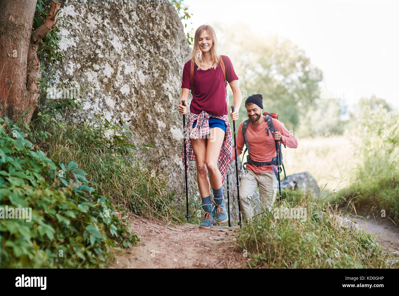 Couple with walking poles hiking in forest, Krakow, Malopolskie, Poland, Europe - Stock Image