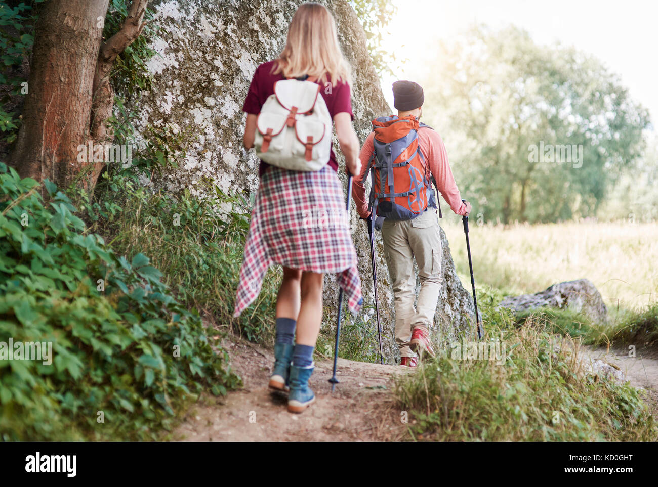 Rear view of couple with walking poles hiking in forest, Krakow, Malopolskie, Poland, Europe - Stock Image