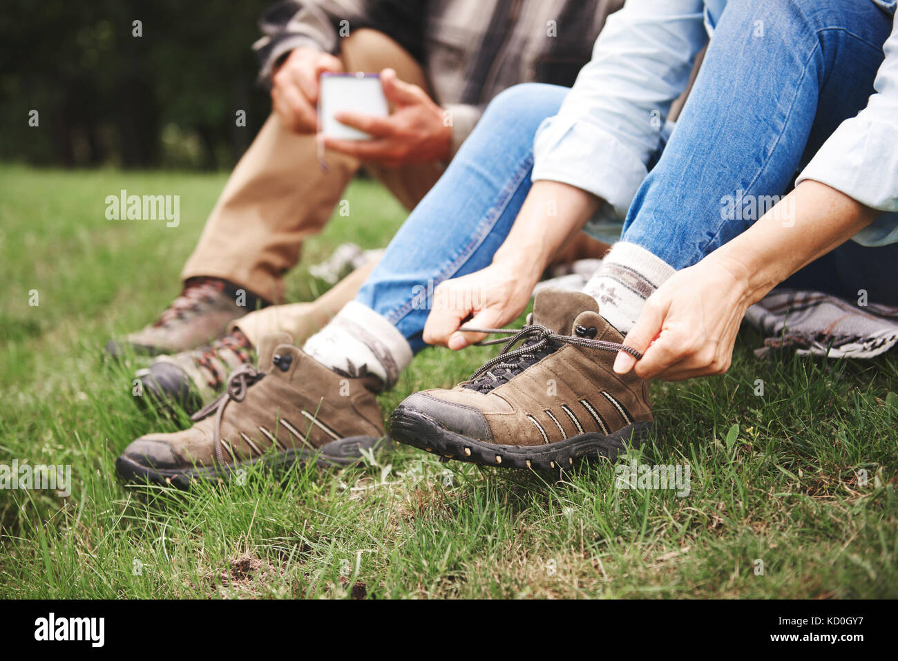 Mature couple sitting on grass, woman tying walking boots, low section Stock Photo