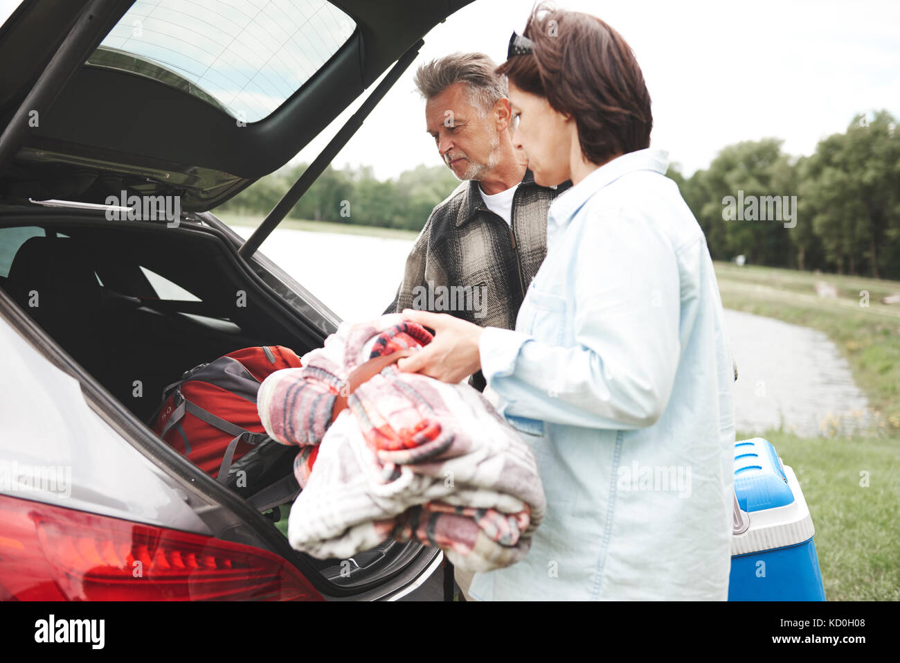 Mature couple removing camping equipment from car boot - Stock Image