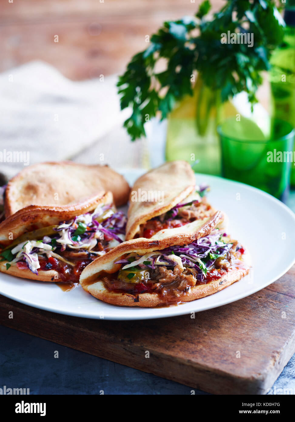 Pulled pork, coleslaw and pickle folded pizza on white plate, close-up - Stock Image