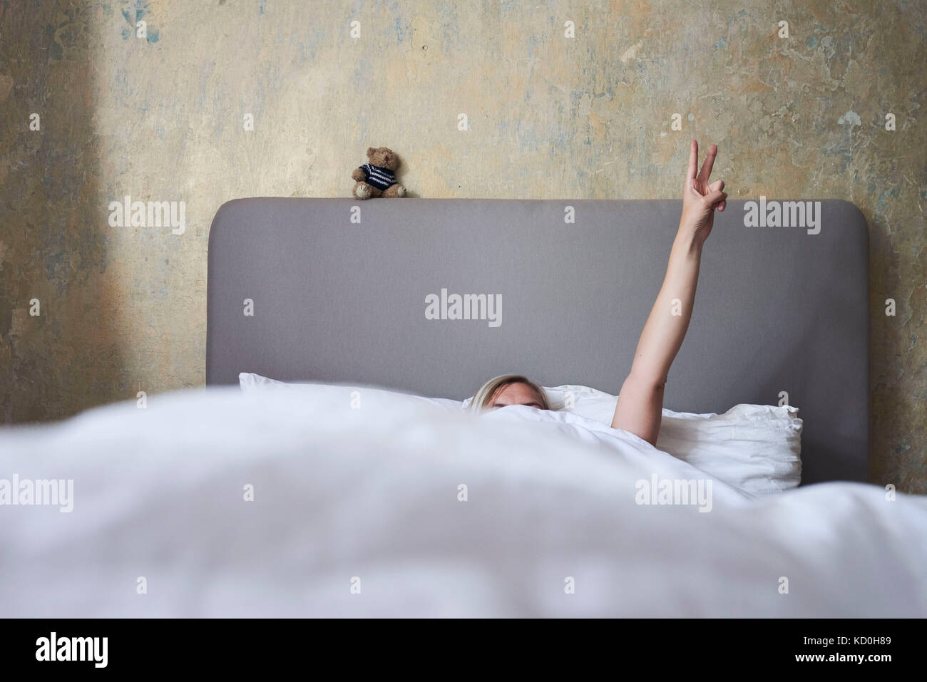 Woman in bed, hiding under covers, arm in air, hand showing peace sign - Stock Image
