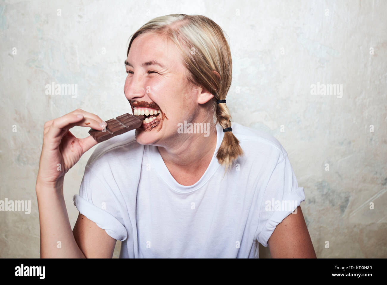 Woman eating bar of chocolate, chocolate around mouth, laughing - Stock Image