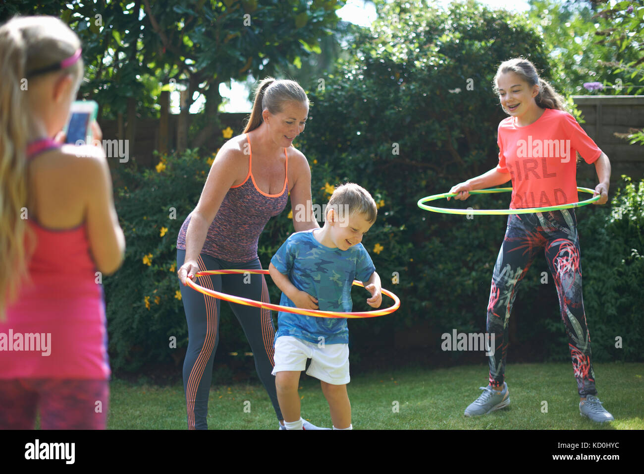 Girl photographing mother and siblings hoola hooping in garden - Stock Image