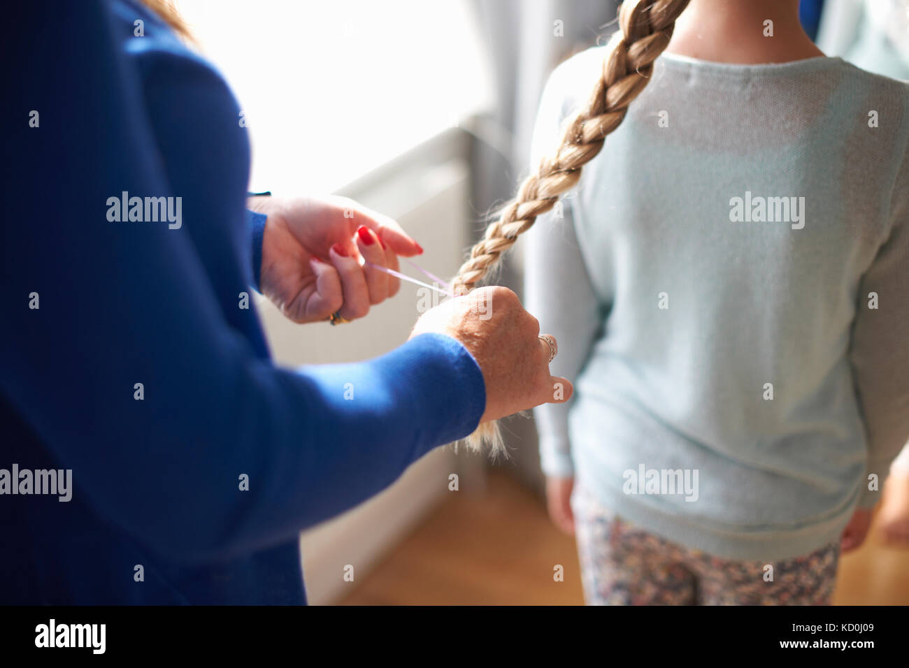 Cropped view of mother plaiting schoolgirl daughter's hair - Stock Image