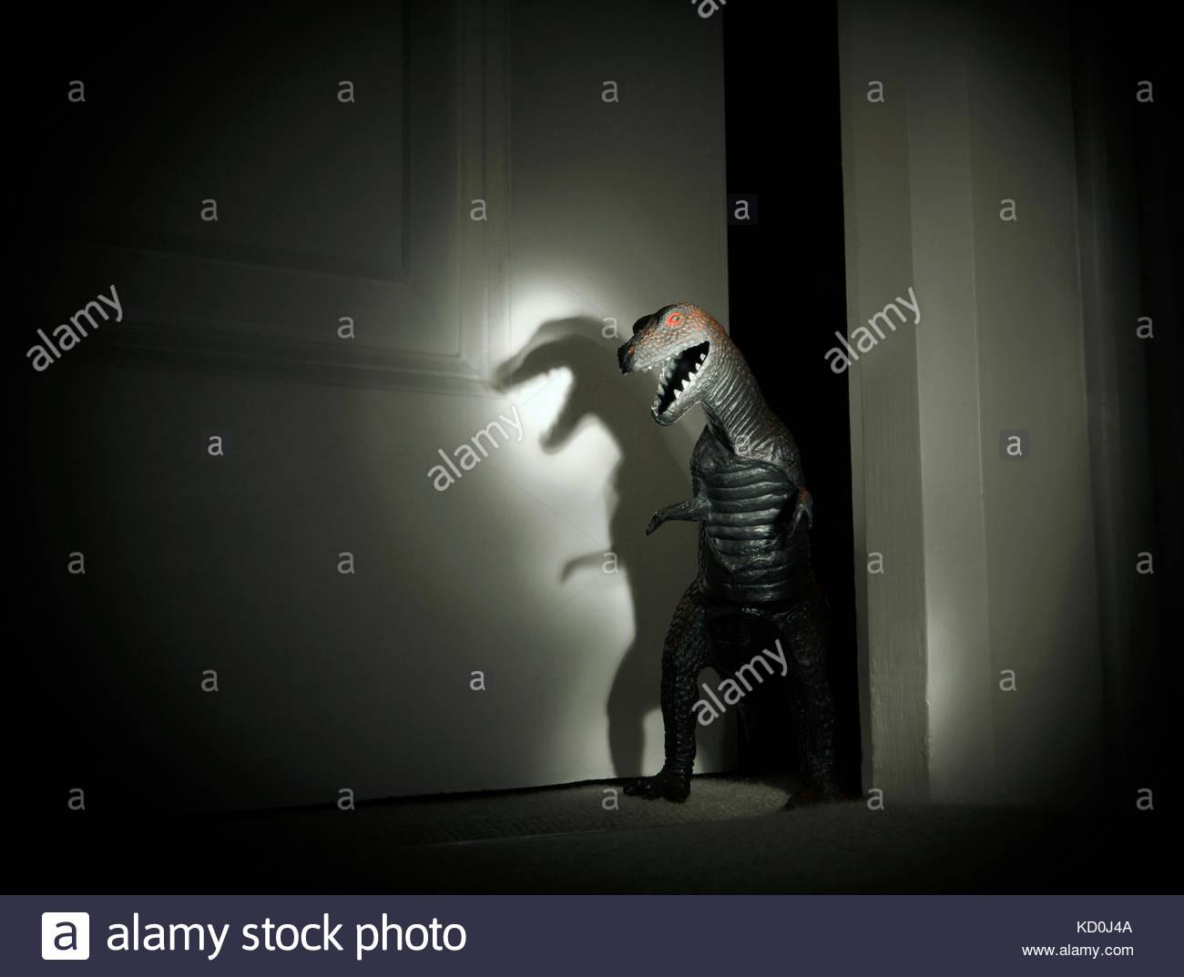 Toy dinosaur spotlit in darkened doorway - Stock Image
