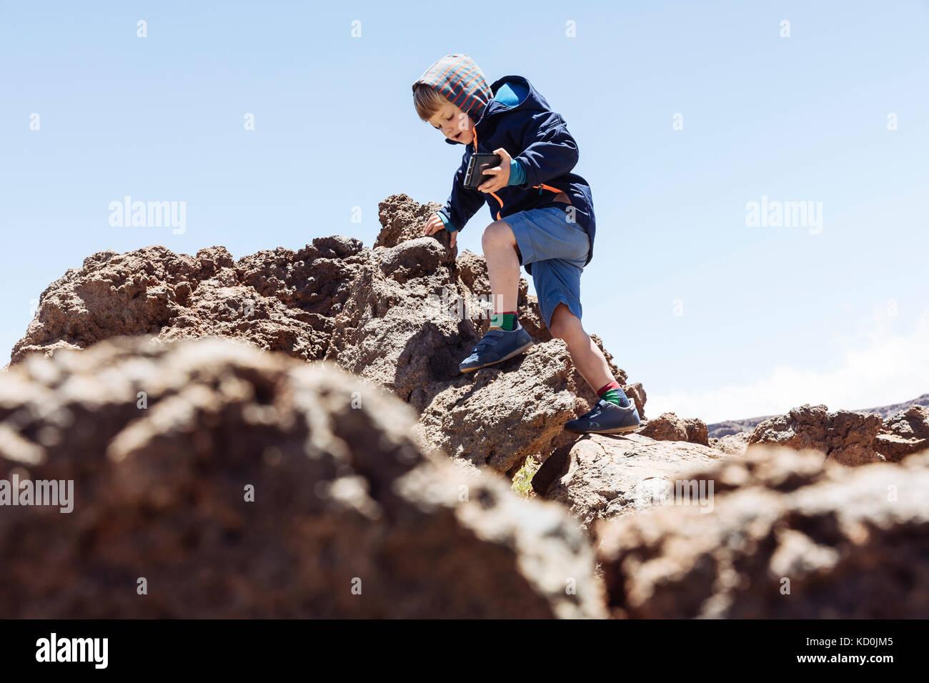 Boy clambering up rocks at Mount Teide, Tenerife, Canary Islands - Stock Image