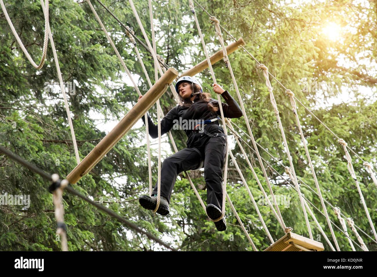 Teenage girl on high rope course - Stock Image