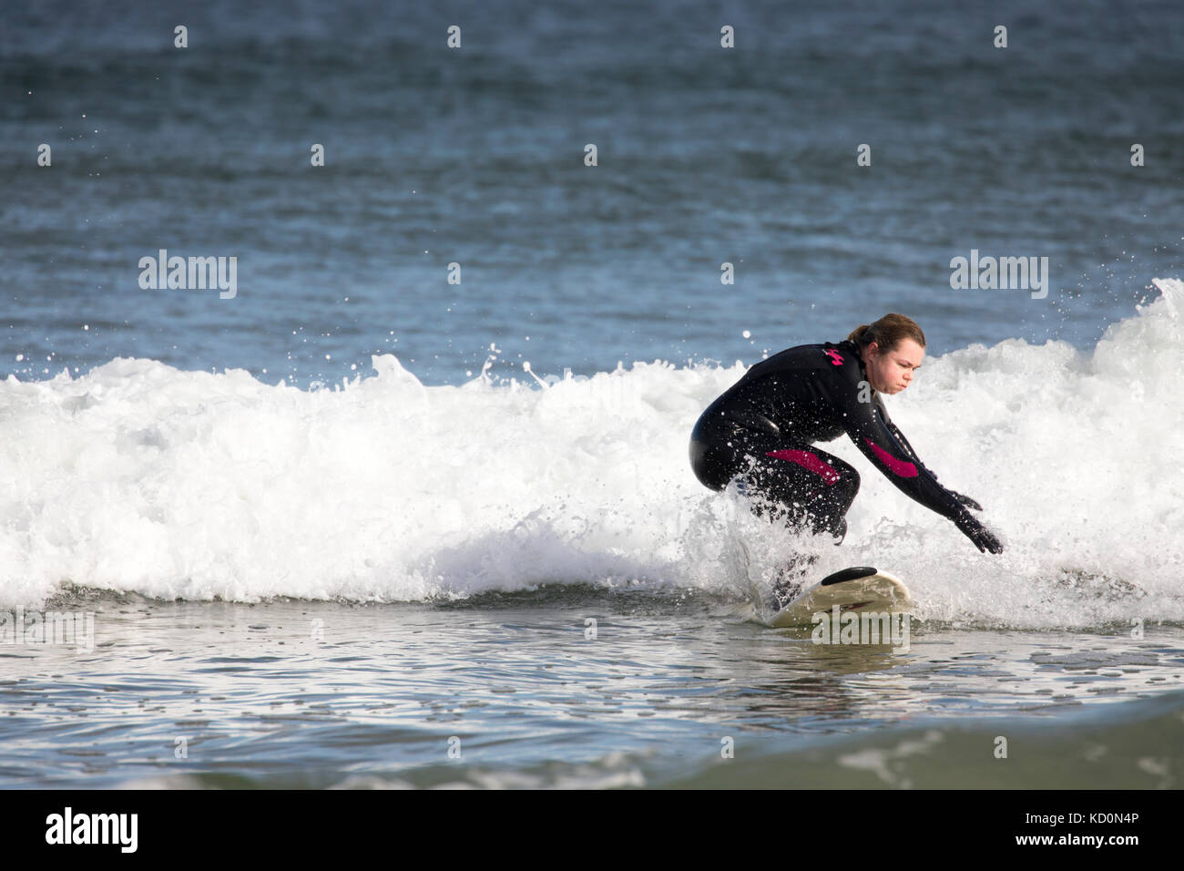 Female surfer riding a wave in the cold waters of