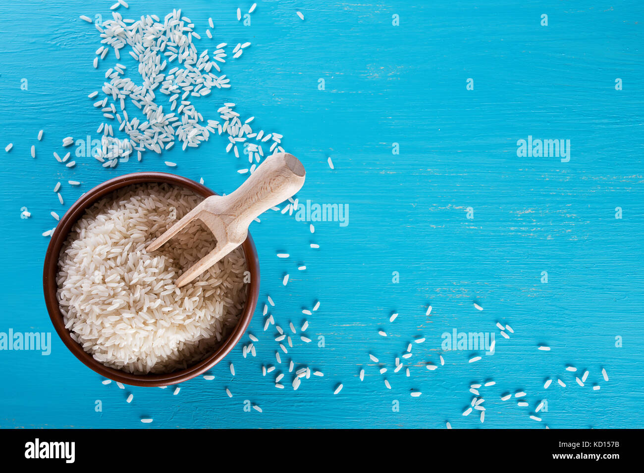 Clay brown plate with raw rice and wooden spatula - Stock Image