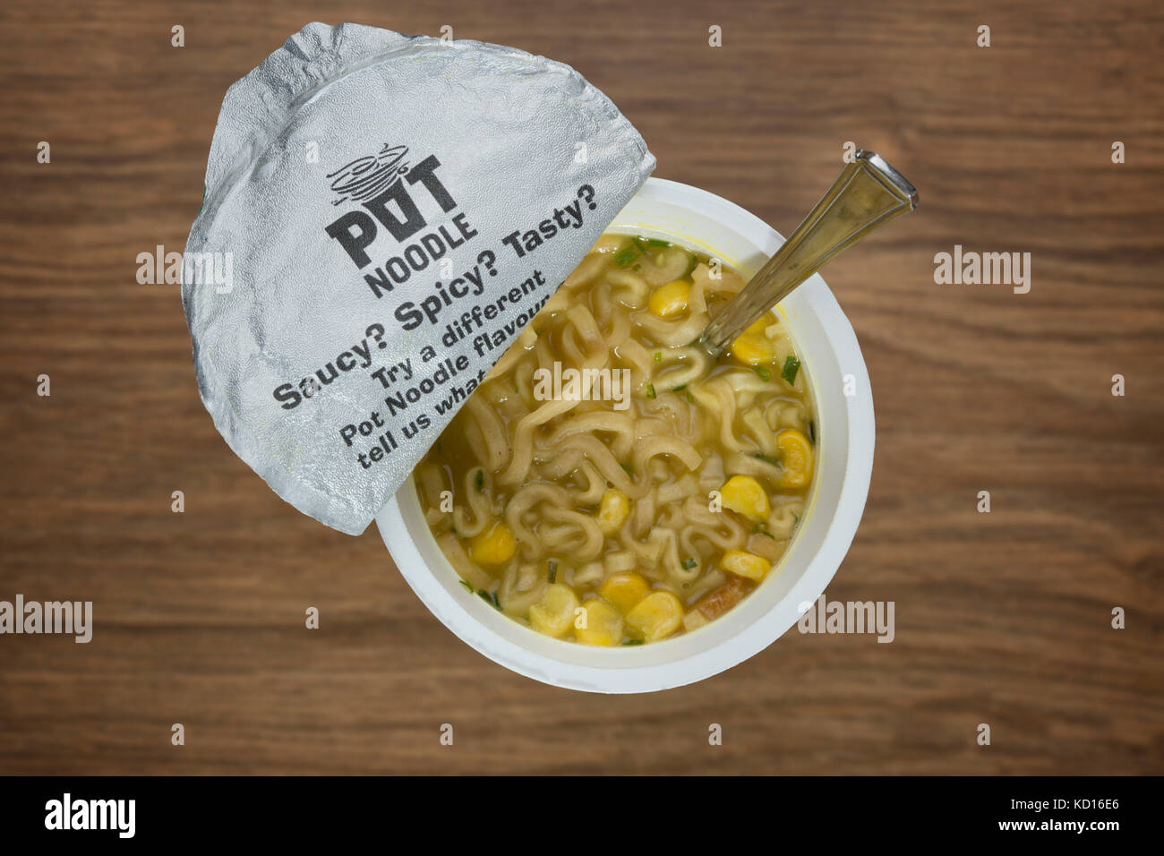 An overhead view of a Pot Noodle (Chicken and Mushroom flavour) in the process of being prepared using boiling water - Stock Image