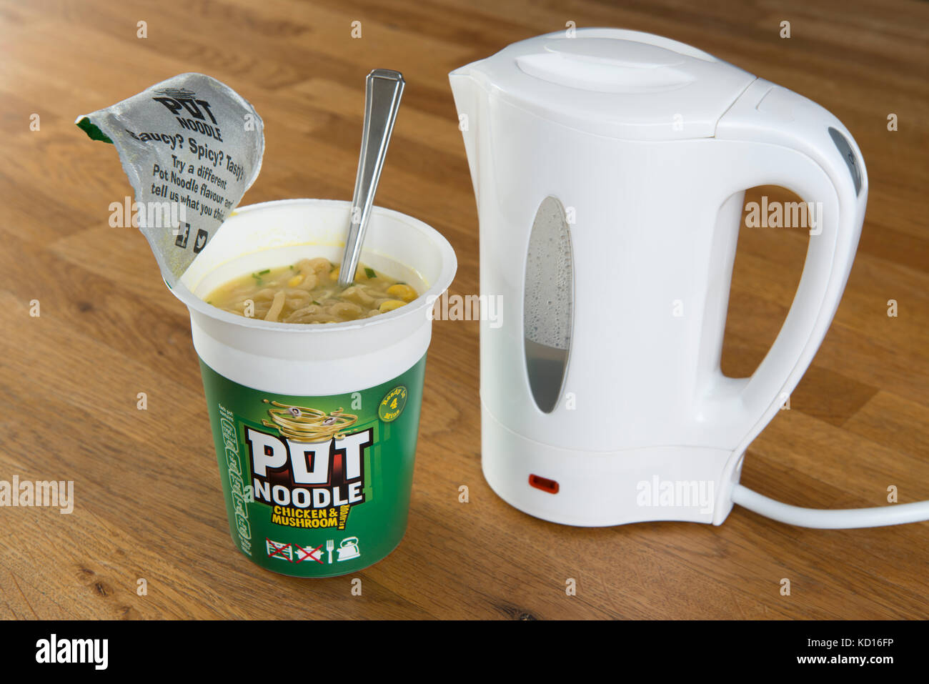 A Unilever Pot Noodle (Chicken and Mushroom flavour) in the process of being prepared using boiling water from a - Stock Image