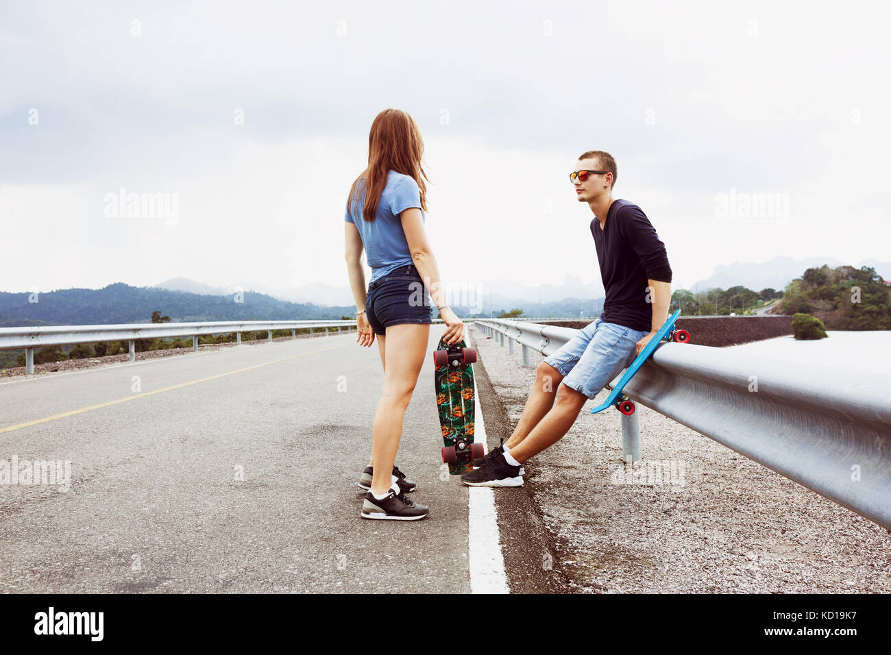 Couple penny skate board road travel - Stock Image
