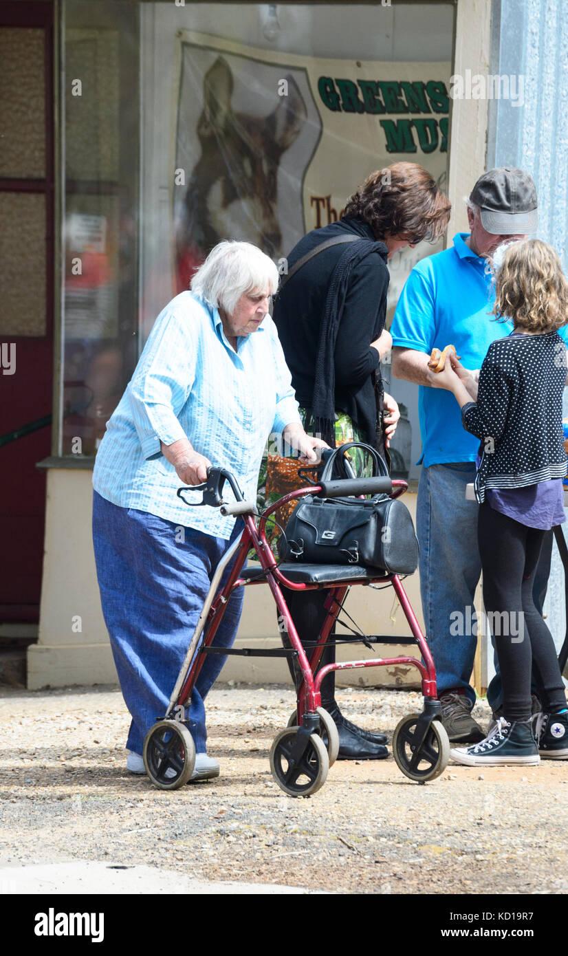 Elderly woman using a walking frame or seat walker in the street ...