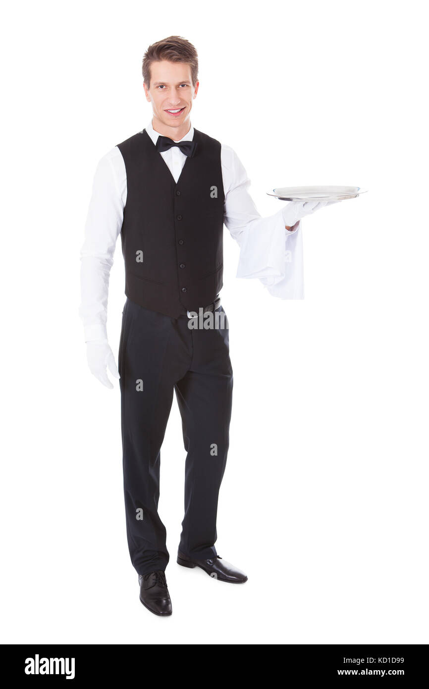 Young Male Waiter Standing With Cloche Lid Cover Over White Background - Stock Image