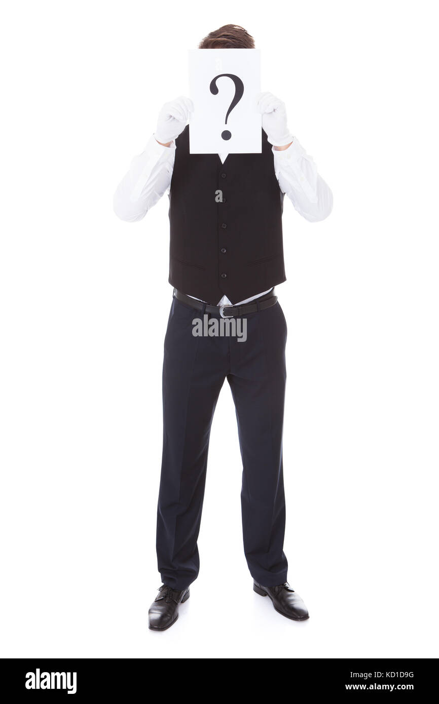 Male Waiter Holding Question Mark On Board Over White Background - Stock Image