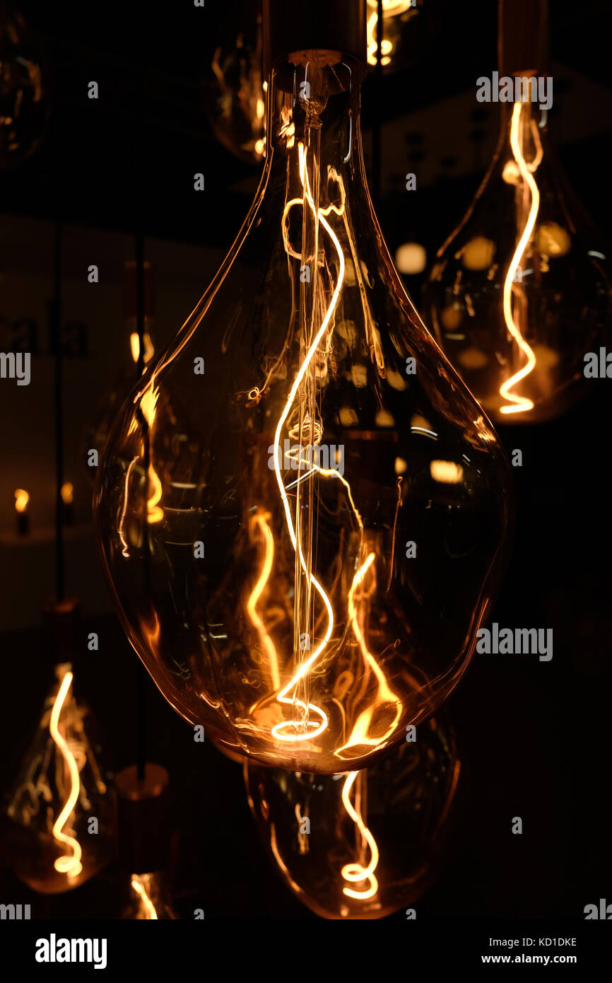 Close up of designer light installation, showing see through glass lamp and light bulb with filament illuminated. - Stock Image