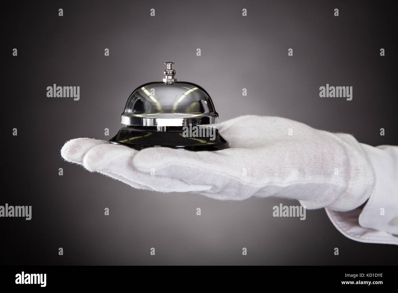 Close-up Of Hand With White Gloves Holding Service Bell - Stock Image